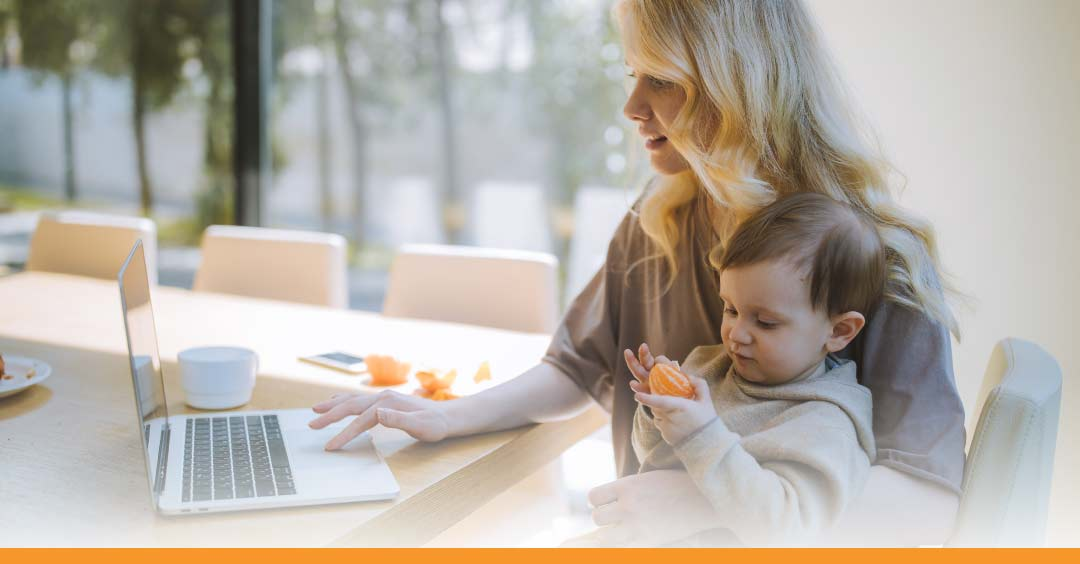 remote working - mother at laptop holding a small child